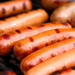 Close up of grilled hot dogs on grill.